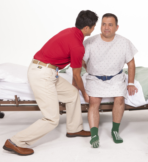 Physical therapist helping a man out of a hospital bed.