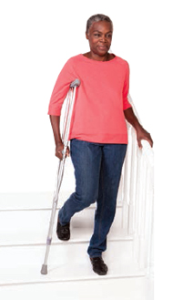 Woman walking down stairs with crutch.