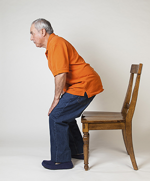 Man standing up from chair.