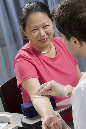 Healthcare provider preparing to draw blood from woman's arm.